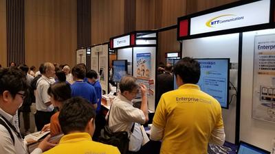 NTTコミュニケーションズ(手前の黄色シャツ)と、NTTテクノクロス(奥の青色シャツ)のブース。